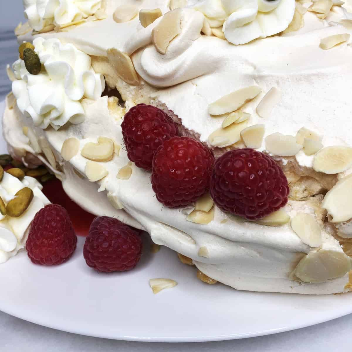 Giant meringue decorated with the piped cream, raspberries and nuts on a white plate