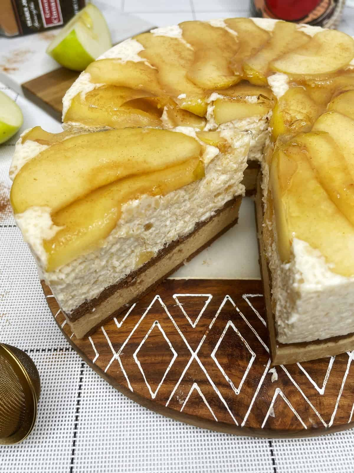 Sliced apple cake featuring caramelized apples on top of the mousse and a chocolate biscuit