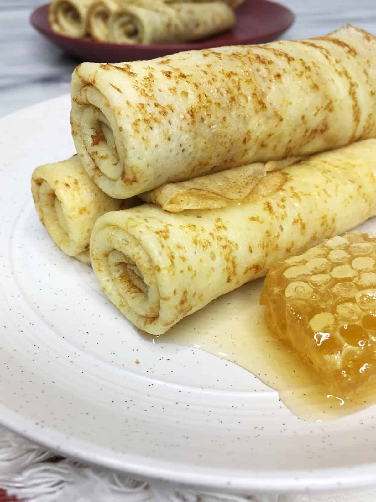 Three rolled crepes with honey aside on a plate