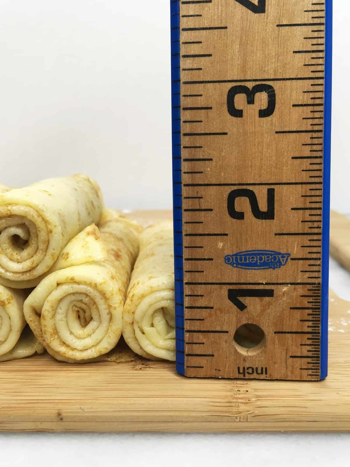 Rolled crepes made according to Authentic French crepes recipe with a wooden ruler on a board
