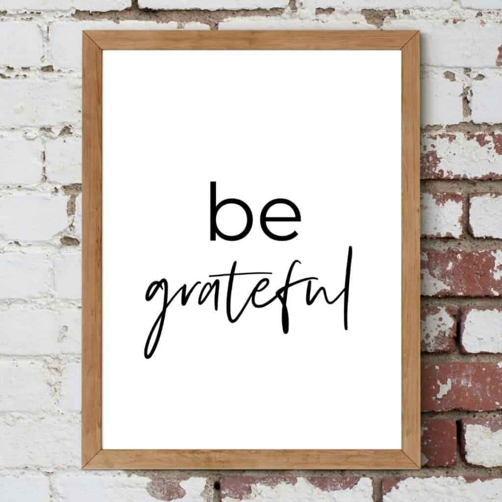 Brown frame on the brick wall with the text: Be grateful