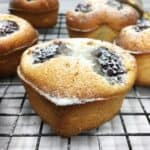 Friands sprinkled with icing sugar on a wire rack