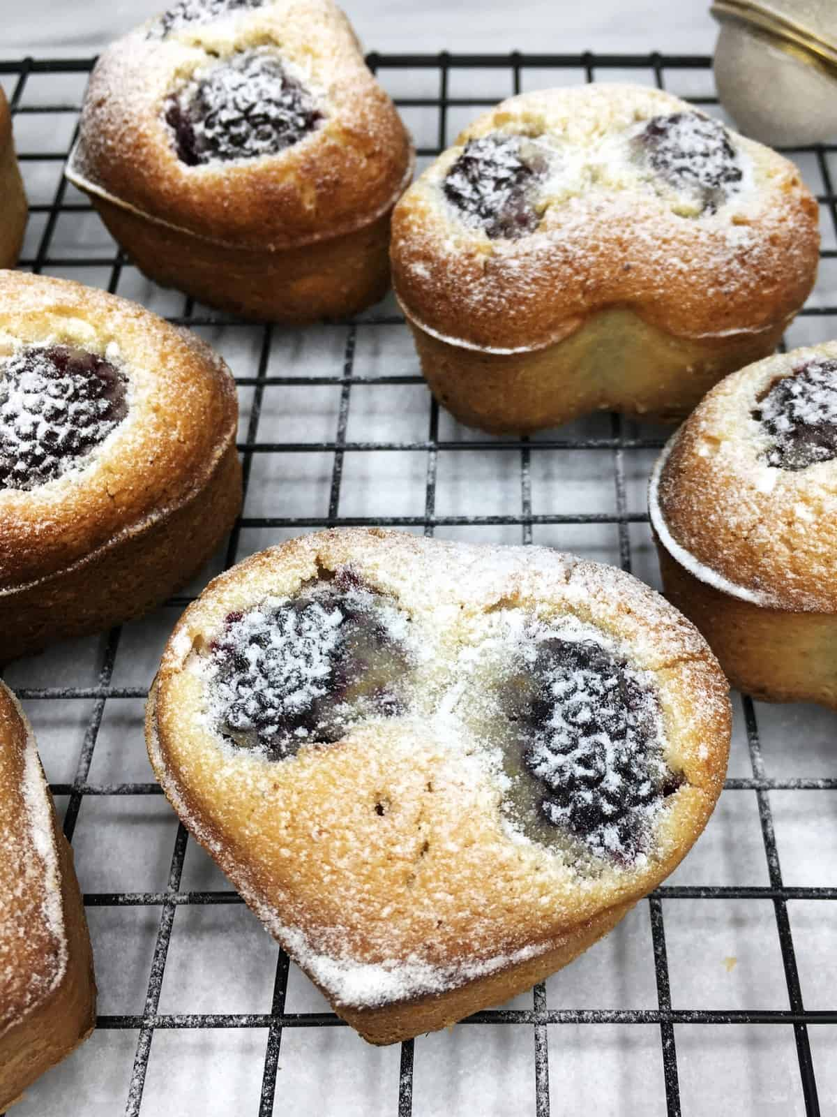 A batch of blackberry friands on a wire rack