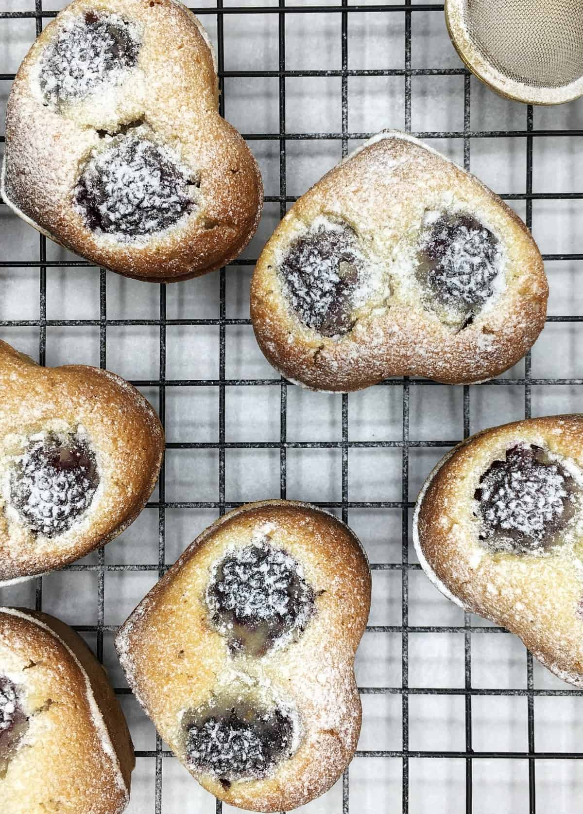 Baked friands with a tea mesh strainer on a wire rack