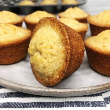 Brown butter French financiers served on a grey plate with a cake pan on background