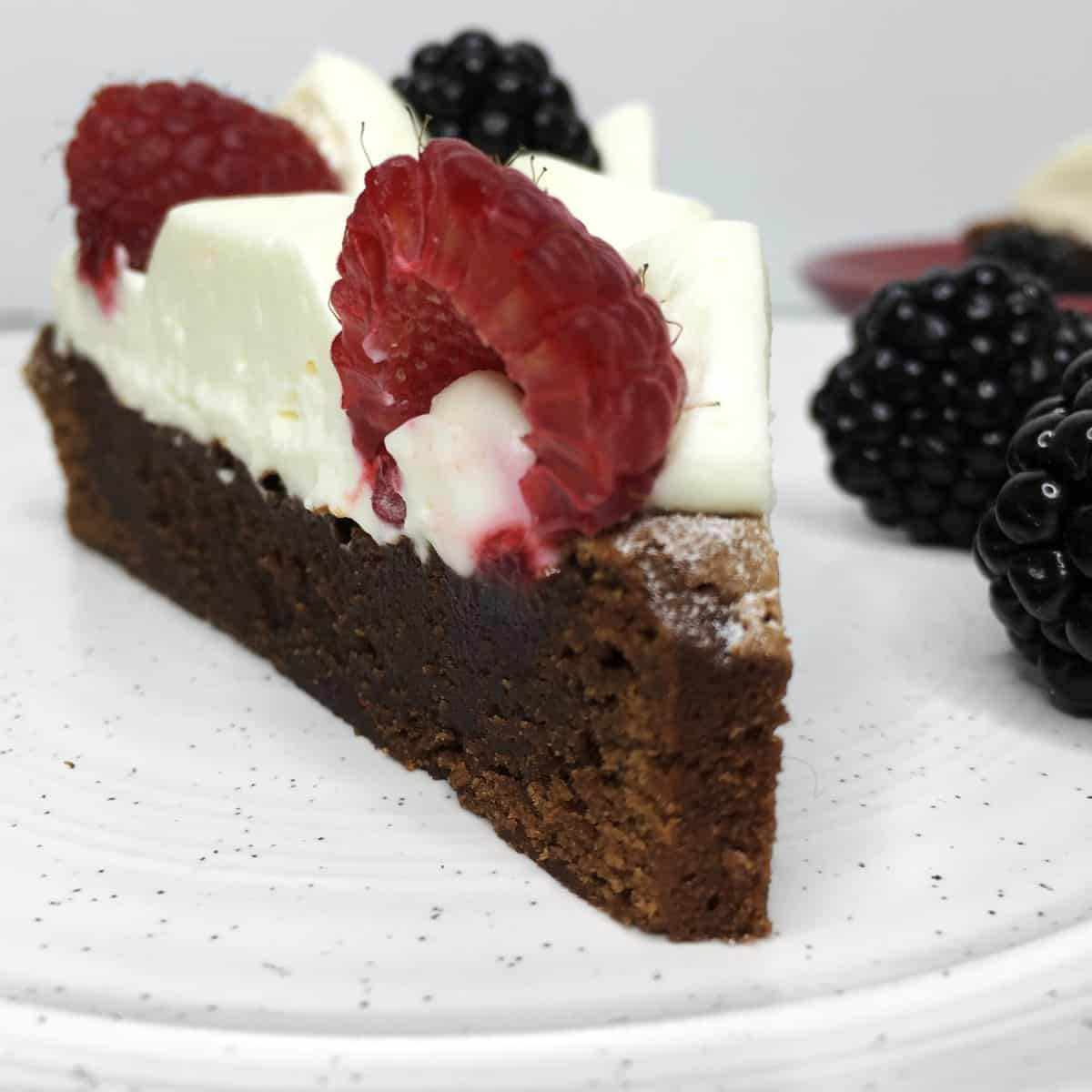 A slice of decorated brownie cake with blackberries on a white plate