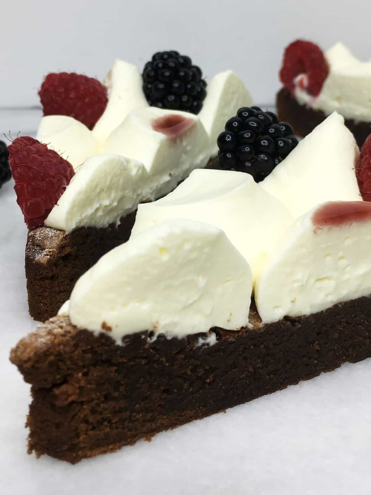A couple of brownies decorated with cream and fresh fruits on a marble board