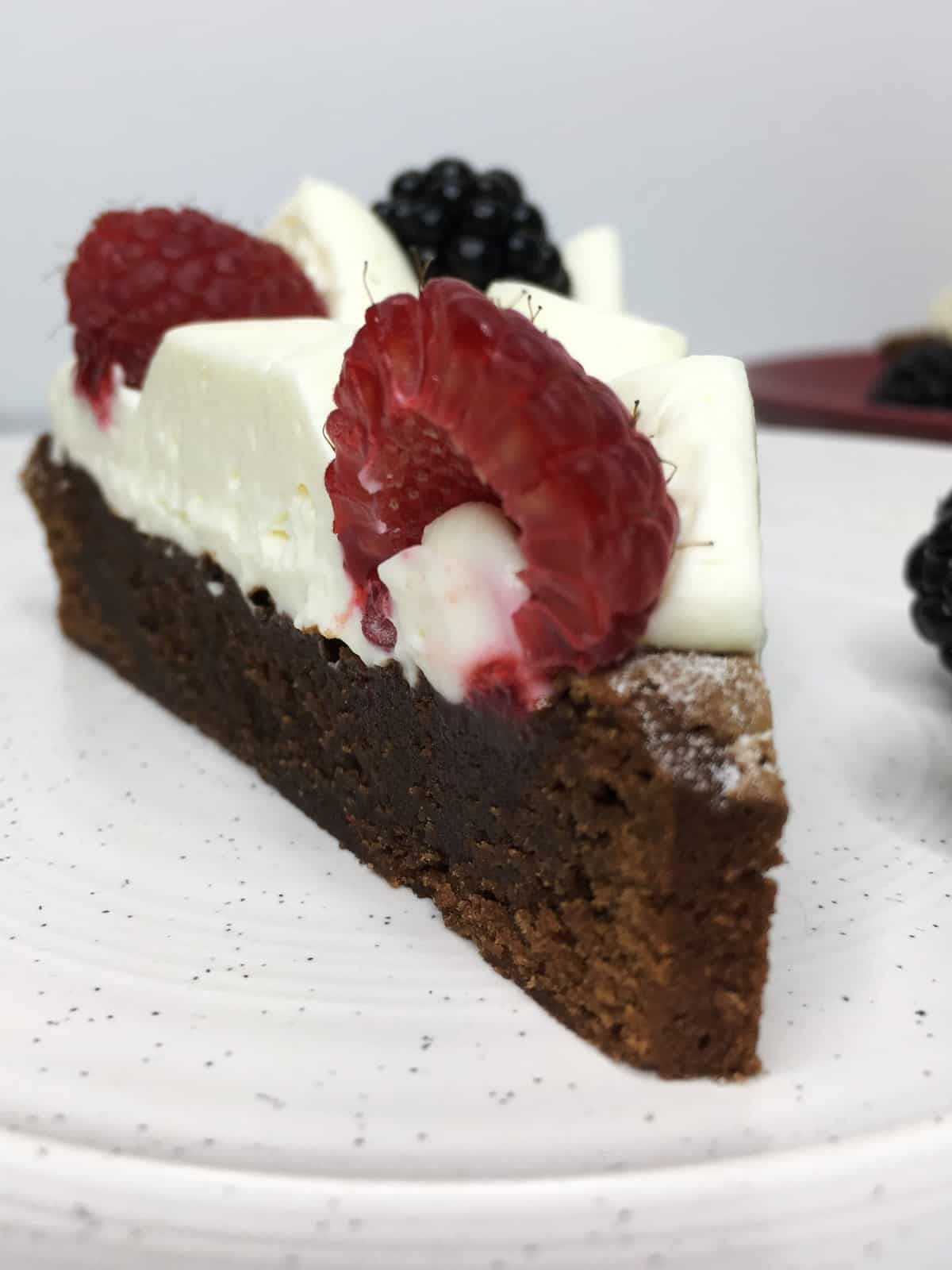 A single brownie slice topped with Chantilly cream and fresh red fruit on a dessert plate