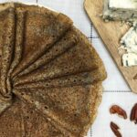 A folded batch of buckwheat crepes with pecans and blue cheese on a board
