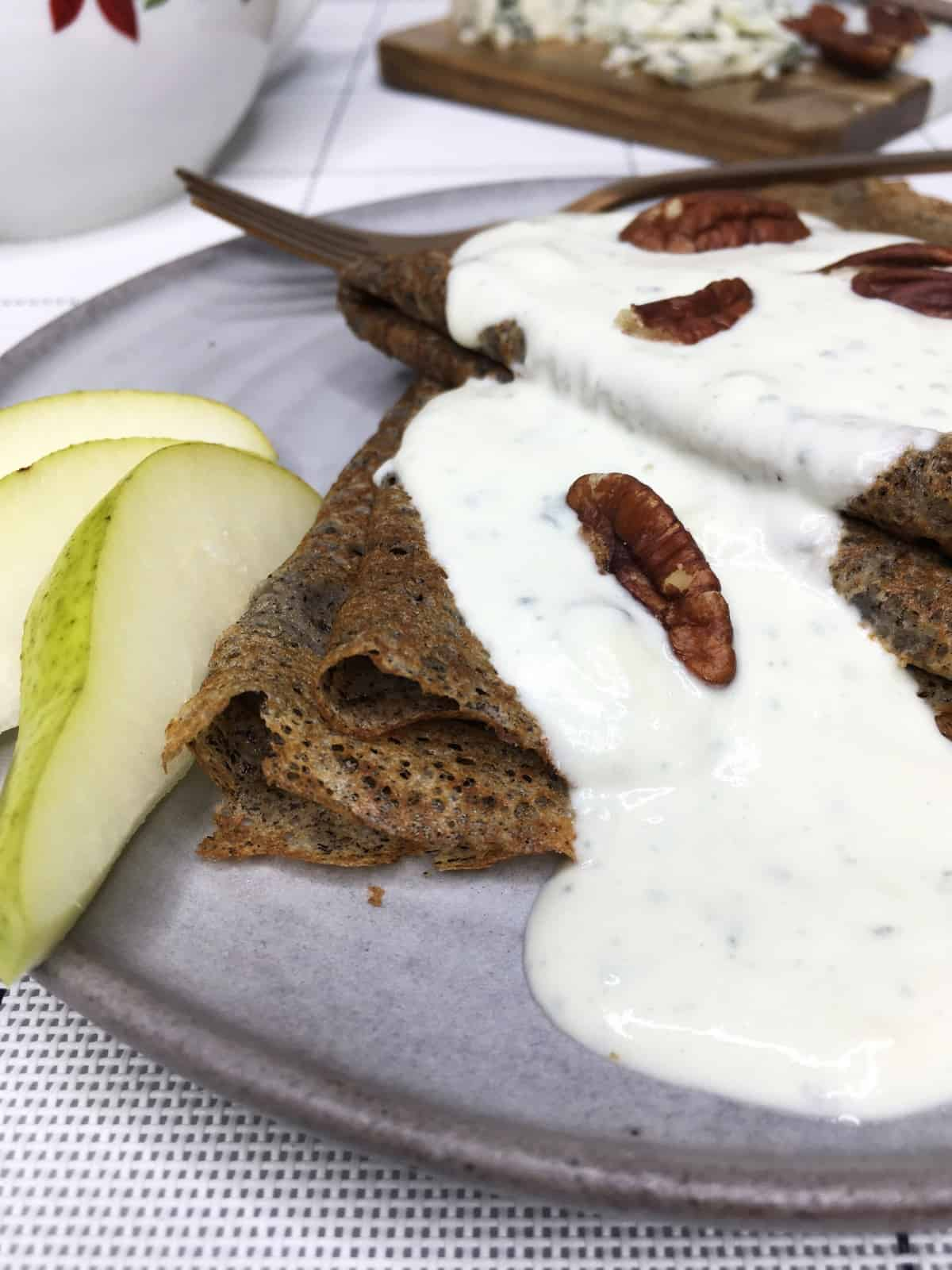 Buckwheat galettes served with blue cheese filling, pecans, sliced pear on a grey plate