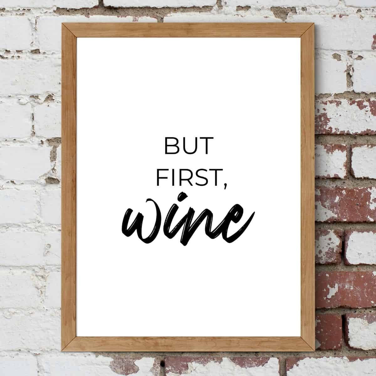 Brown frame on the brick wall with the text: But first, wine