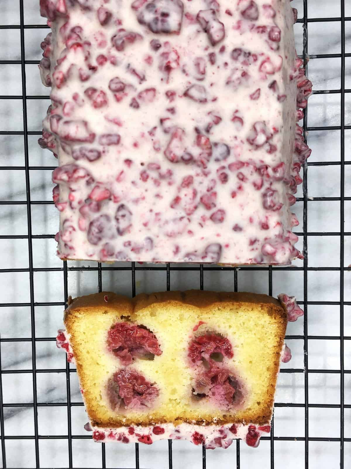 Raspberry loaf cake with the white chocolate and dried raspberry glaze on a rack and a slice aside: Overhead view