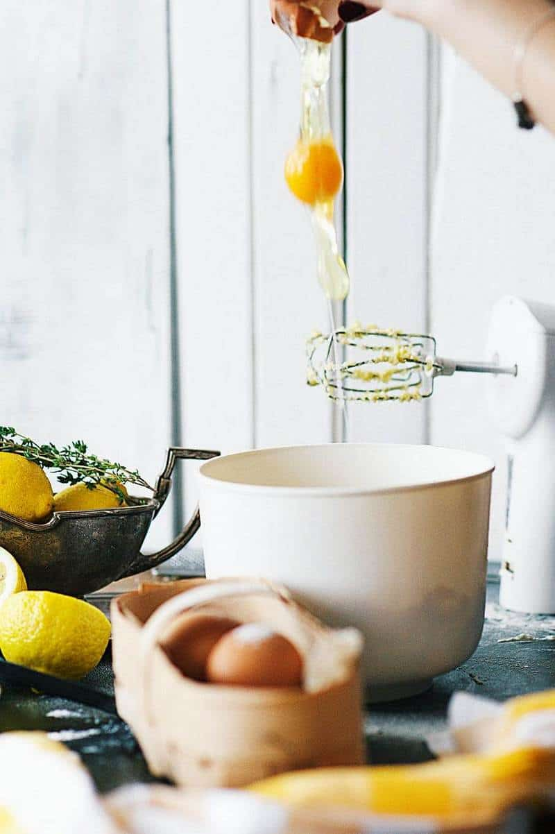 Cracked egg over a bowl with other eggs, lemons and electric mixer on background