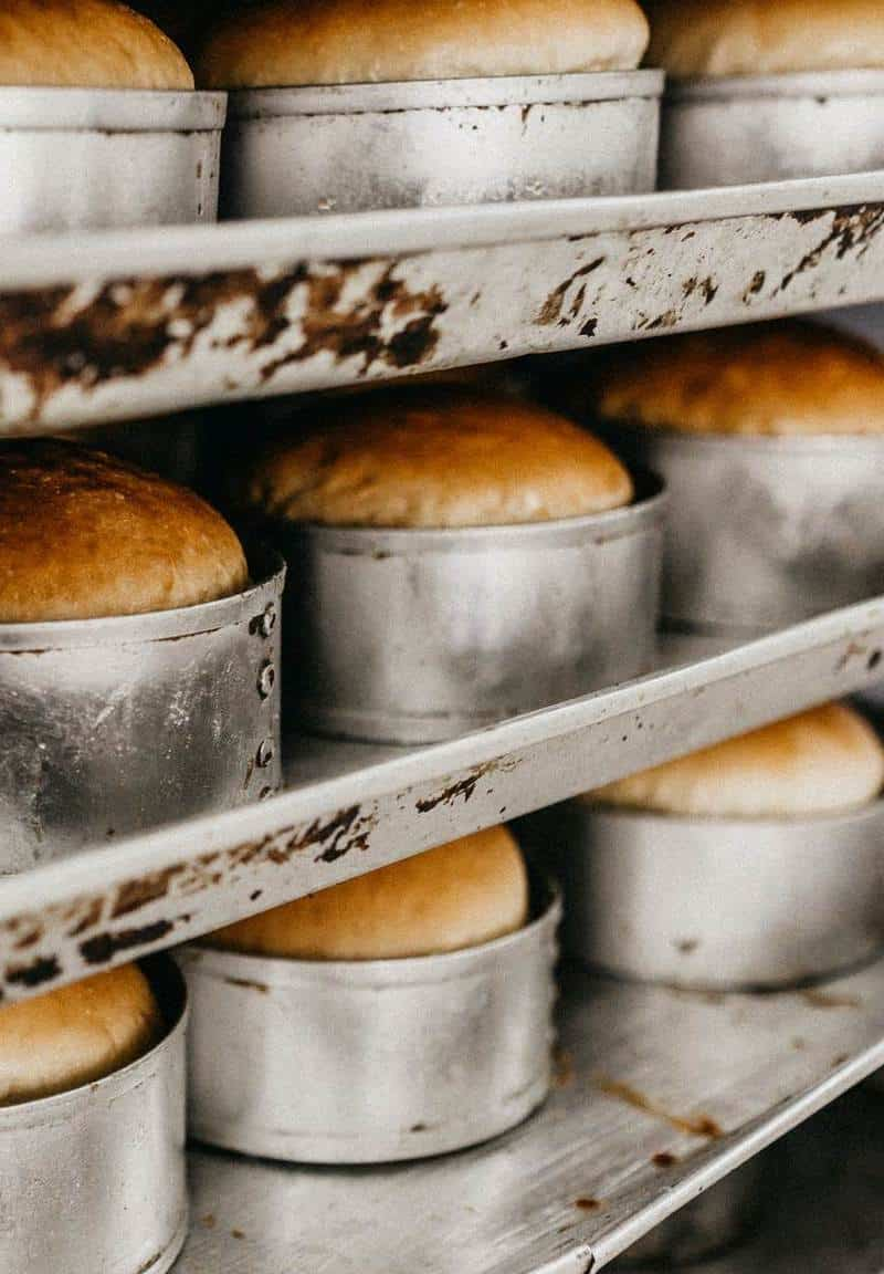 Baked bread in cake pans on commercial baking sheets