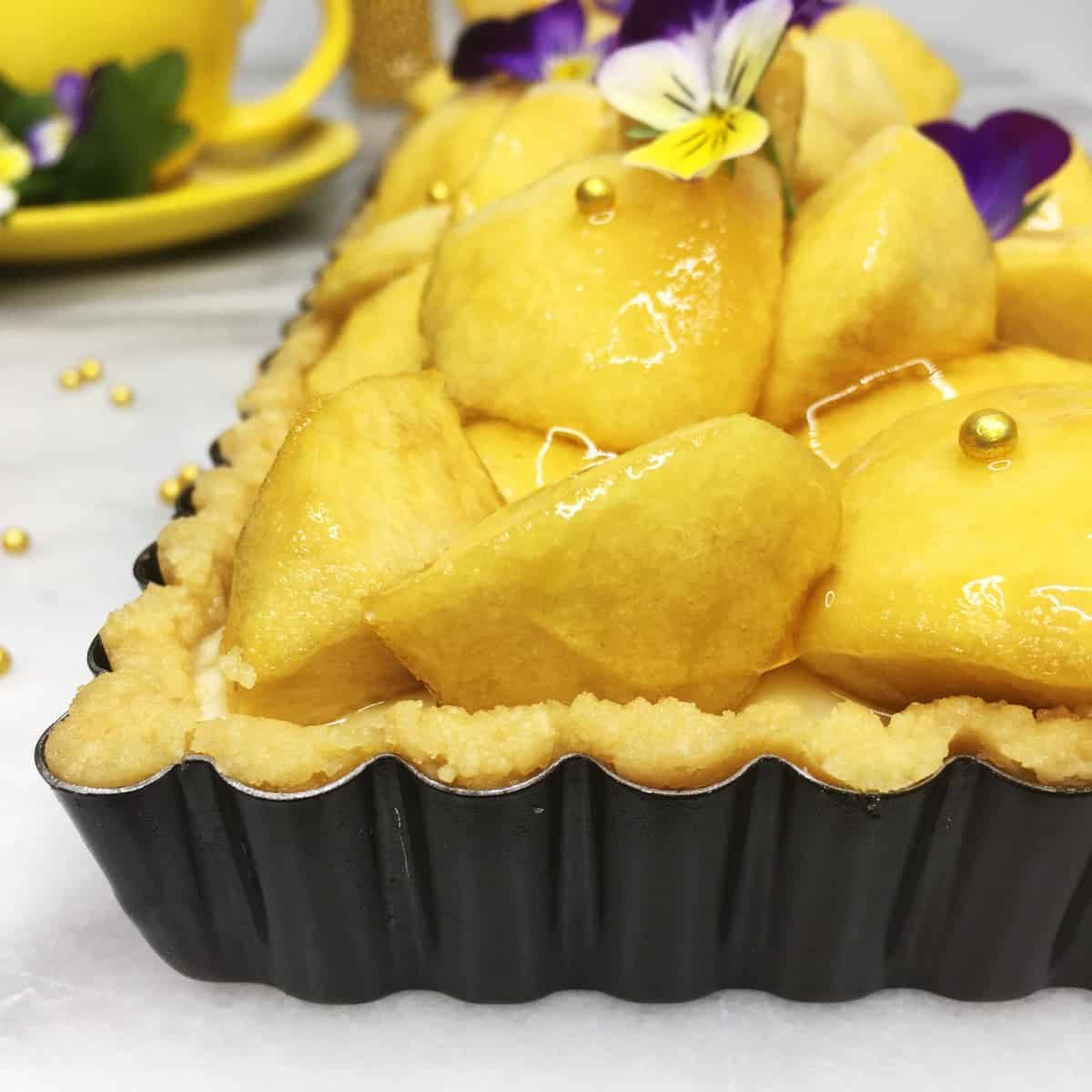 Apple tart decorated with gold pearls and flours in a tart pan with a yellow cup on the background