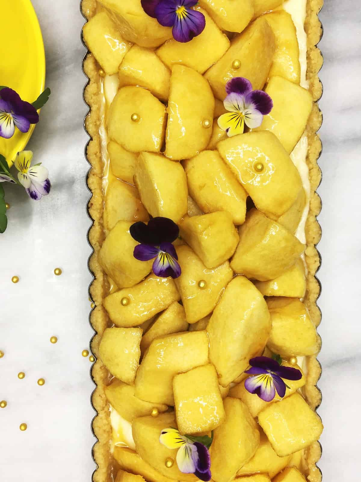 French apple tart garnished with apples in a tart pan with a yellow cup and glod pearls on the background