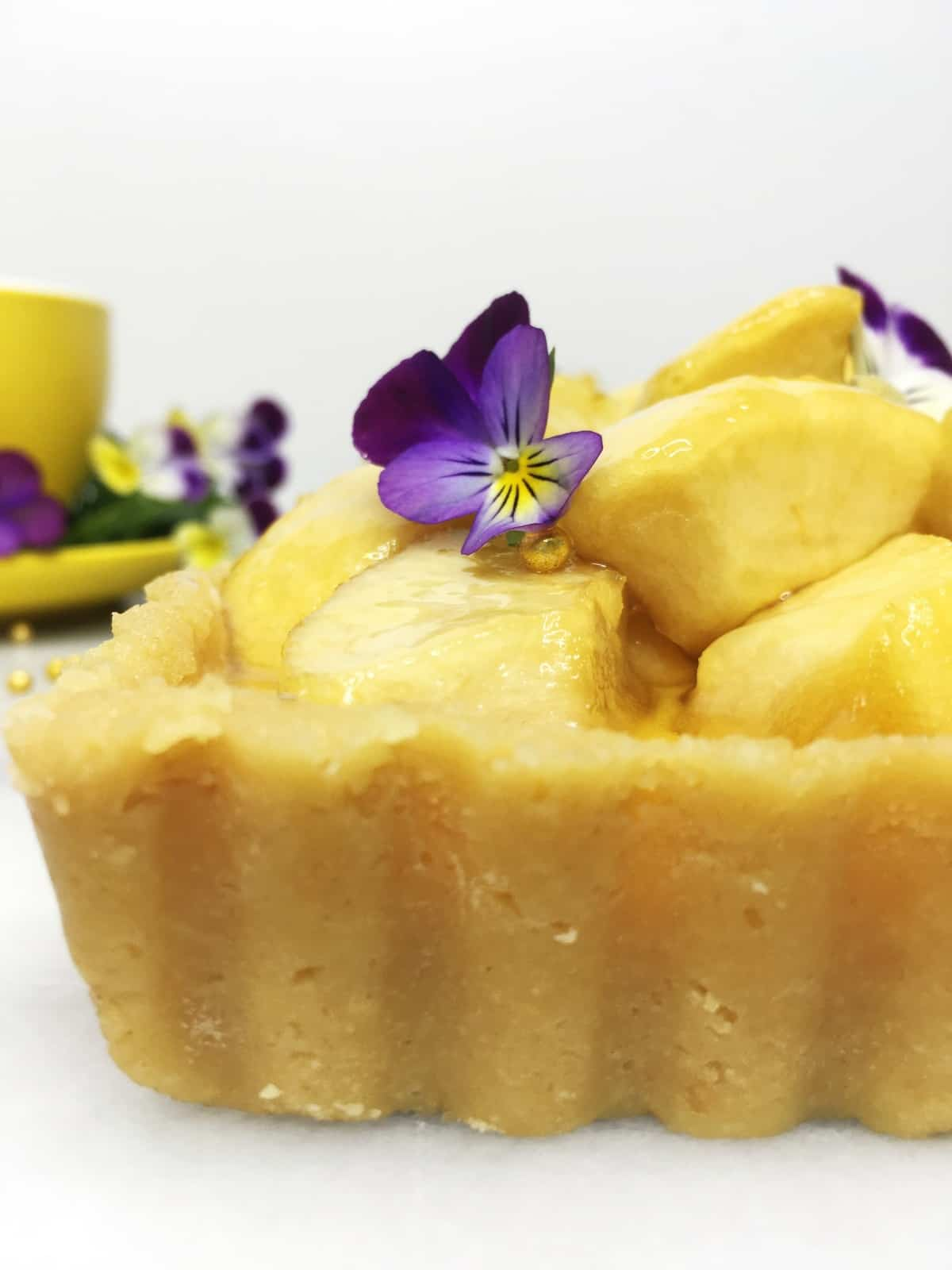 Tart loaded with caramelized apples and decorated with flours with a cup on the background