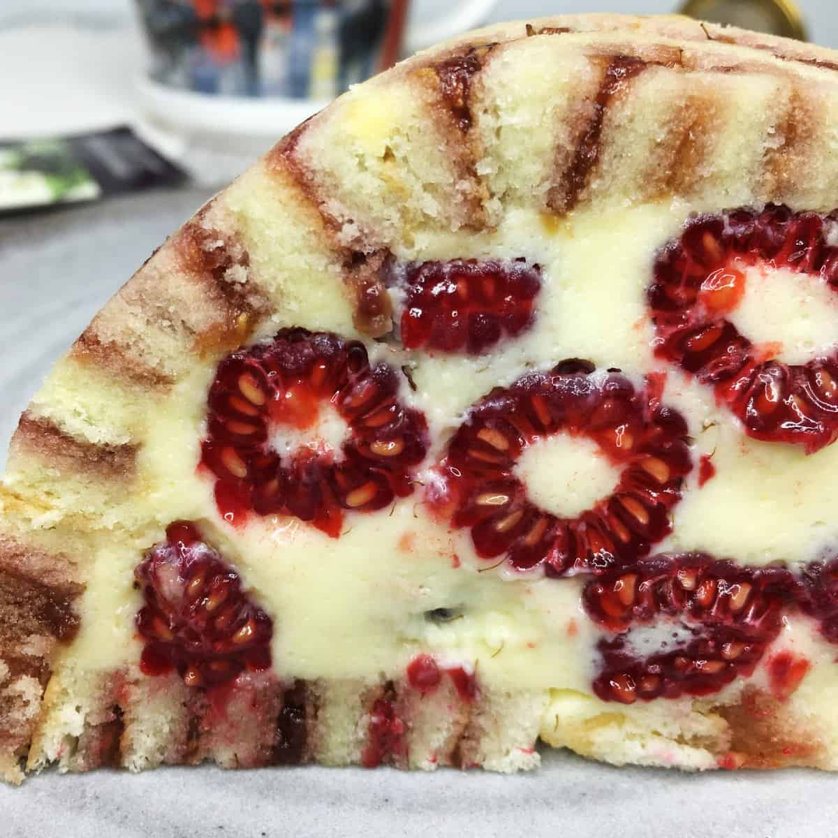 A slice of Charlotte Royale cake packed with fresh raspberries on a grey plate: Close up