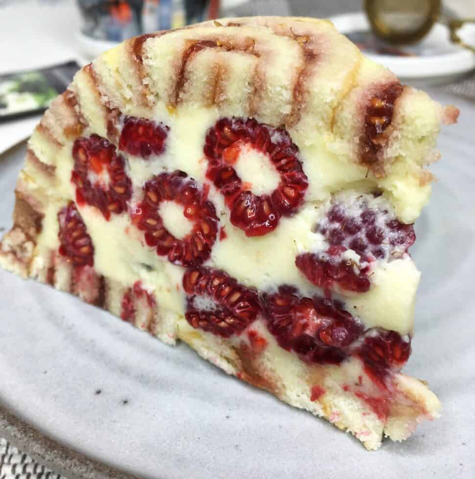 A slice of Charlotte royale cake filled with raspberries on a grey dessert plate