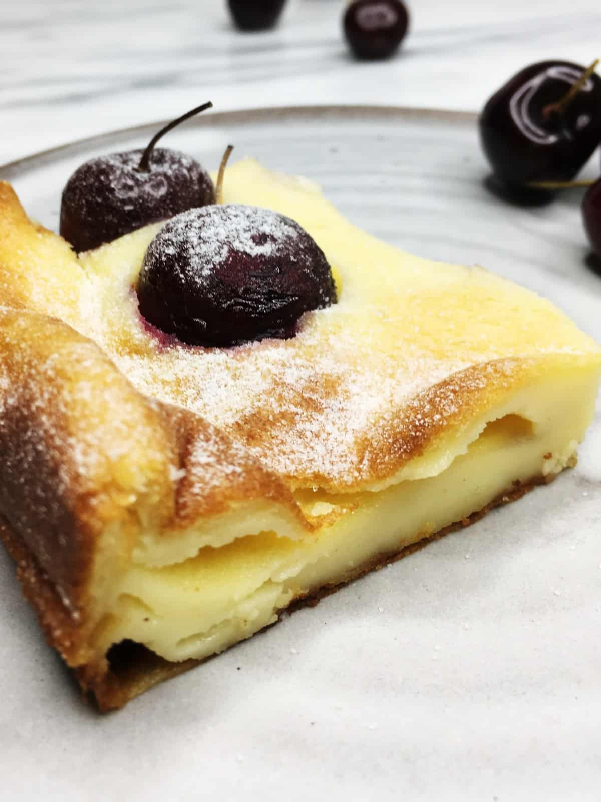 A square piece of French cherry dessert with cherries on a grey plate