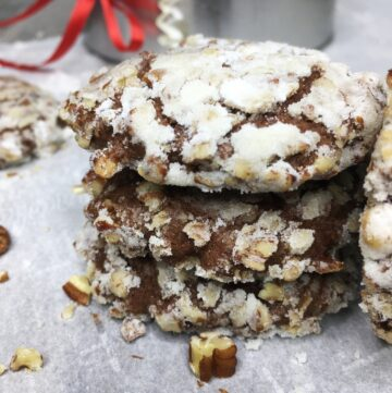 Stacked chocolate banana cookies with a gift tin and pecans in the background