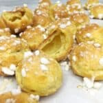 Multiple baked chouquettes on parchment paper