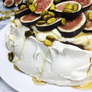 Pavlova topped with cream, figs, honey and pistachios. Served on a white plate: Close Up