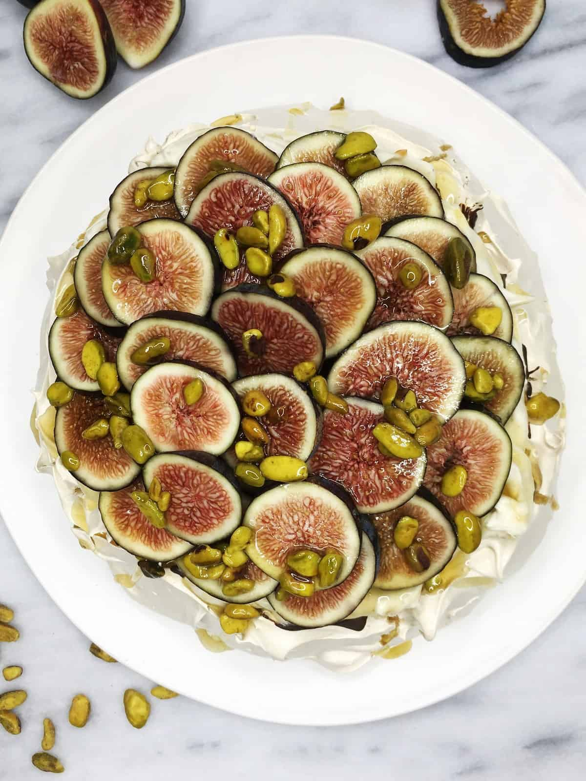 Decorated Pavlova cake on a white plate with figs and pistachios on a marble board: Overhead view