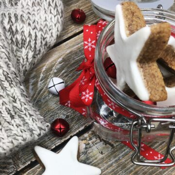 A batch of the glazed cinnamon cookies in a jar with a scarf and a cookie on a wooden surface
