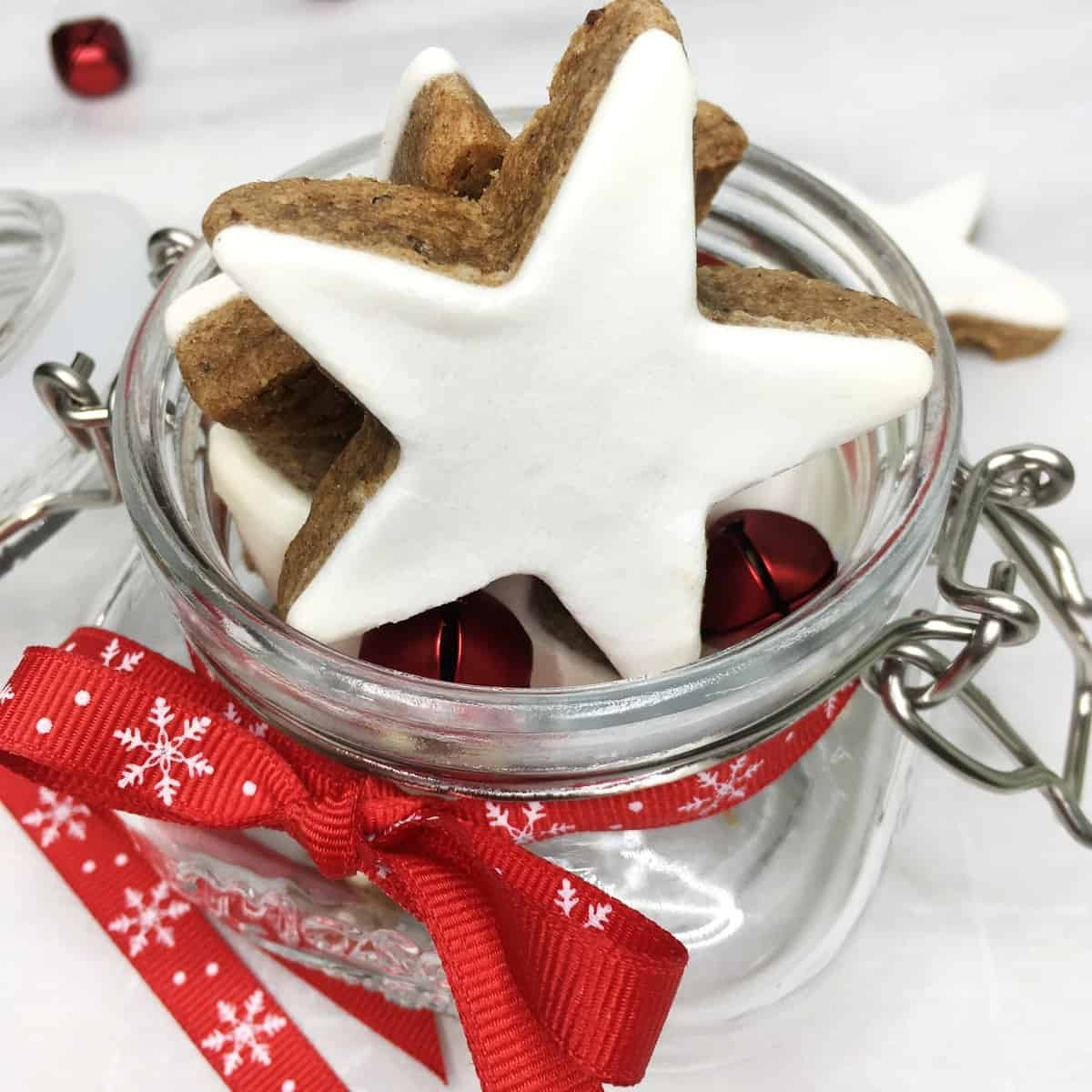 Star-shaped cookies coated with white glaze in a glass jar tied with the red ribbon