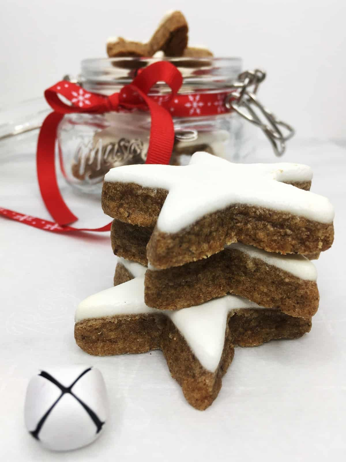 Three star-shaped cookies with a glass jar full of cookies on background