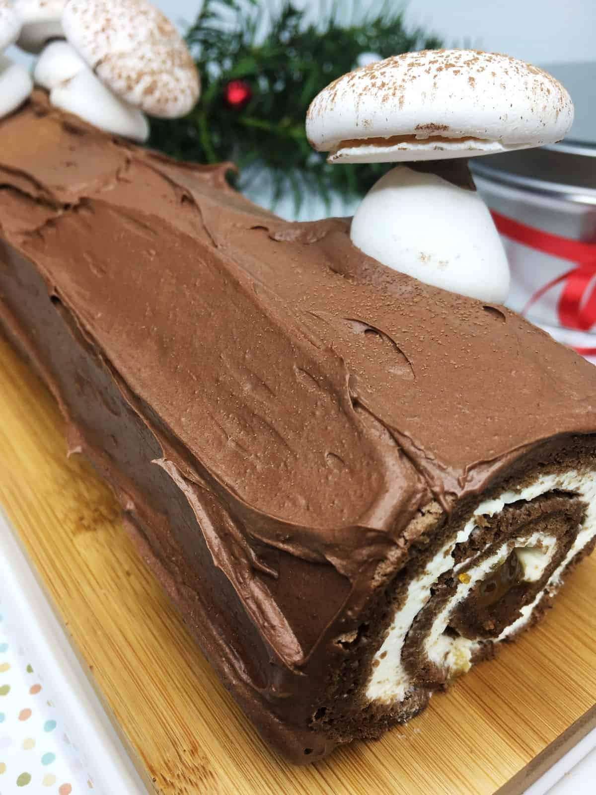 Christmas Yule log covered with chocolate frosting and decorated with meringue mushrooms on a wooden board