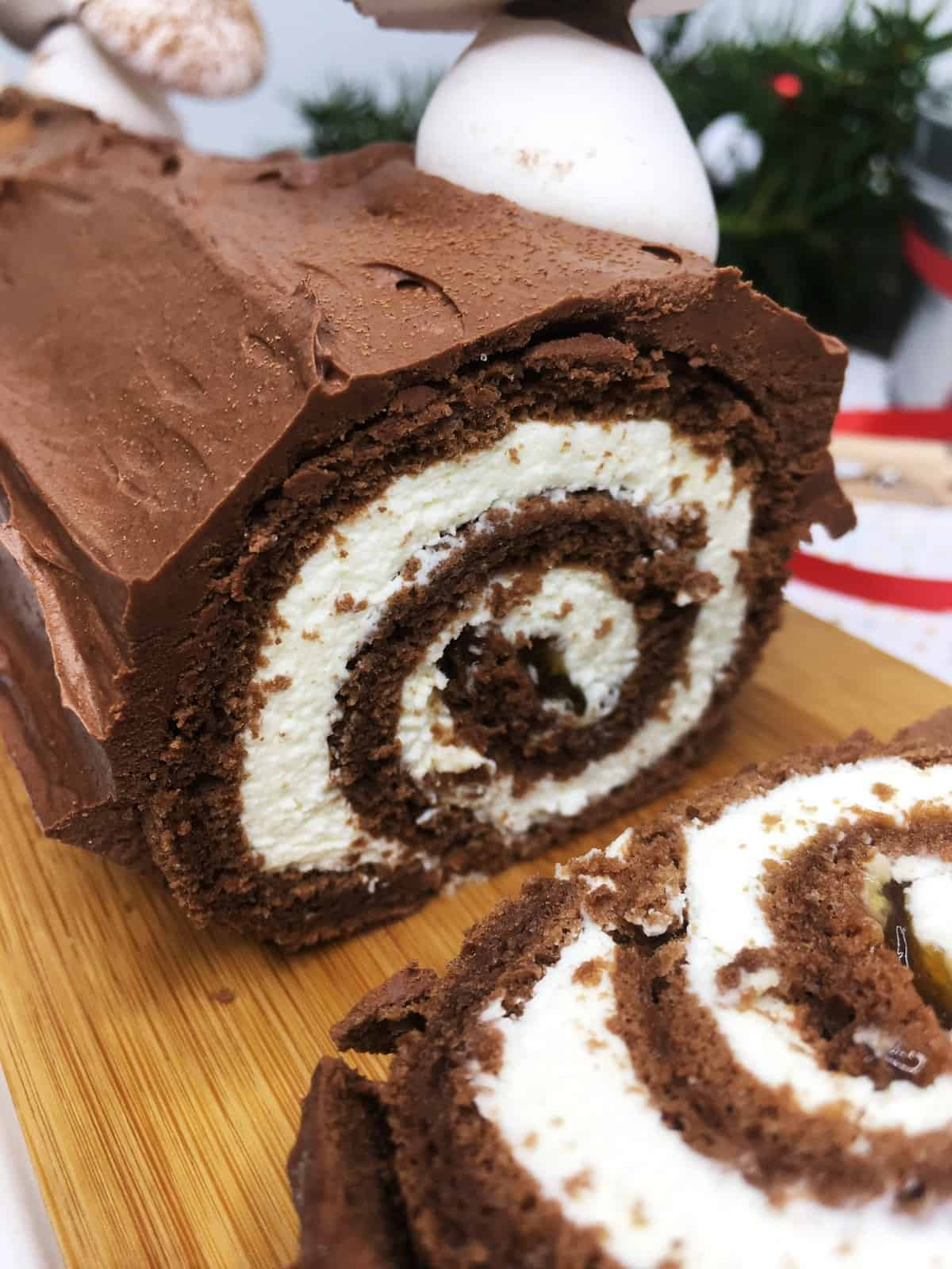 Rolled and decorated Buche de Noel with a swirl on a wooden board: Close up
