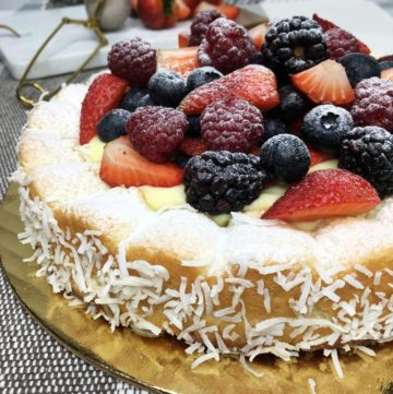 Coconut Dacquoise Cake served on a cake platter with a board and fruits on background