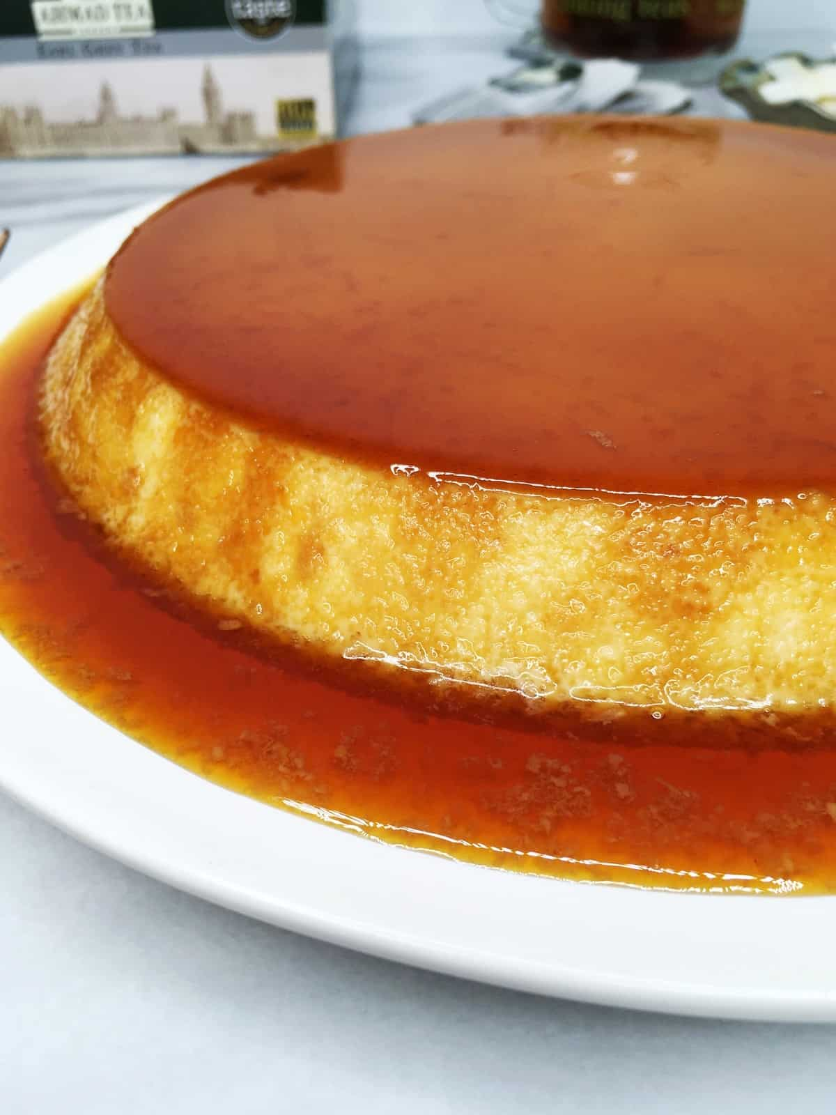 Flan topped with caramel and tea box, tea bags and a cup in the background