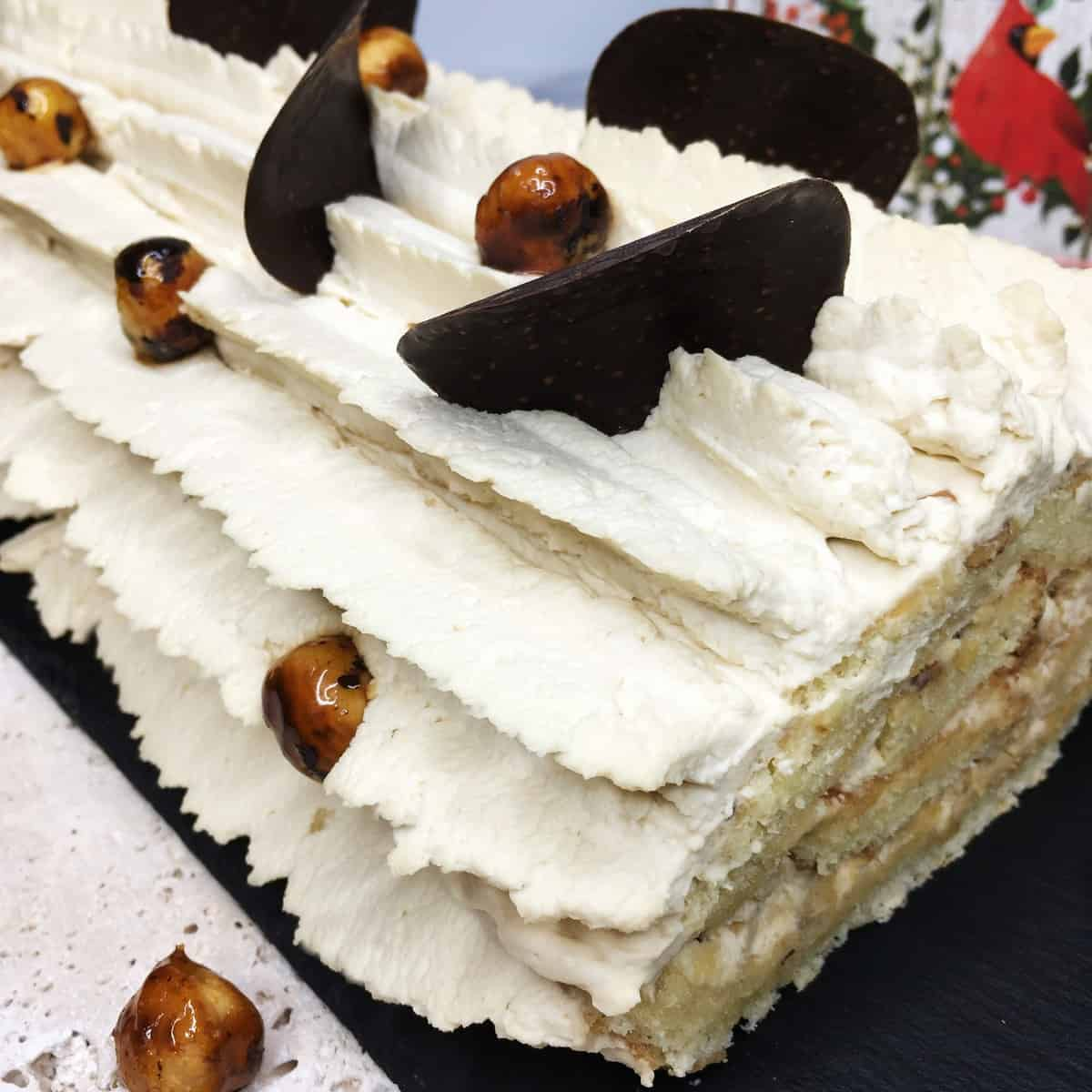 Coffee roll cake garnished with cream and decorated with chocolate and caramelized nuts