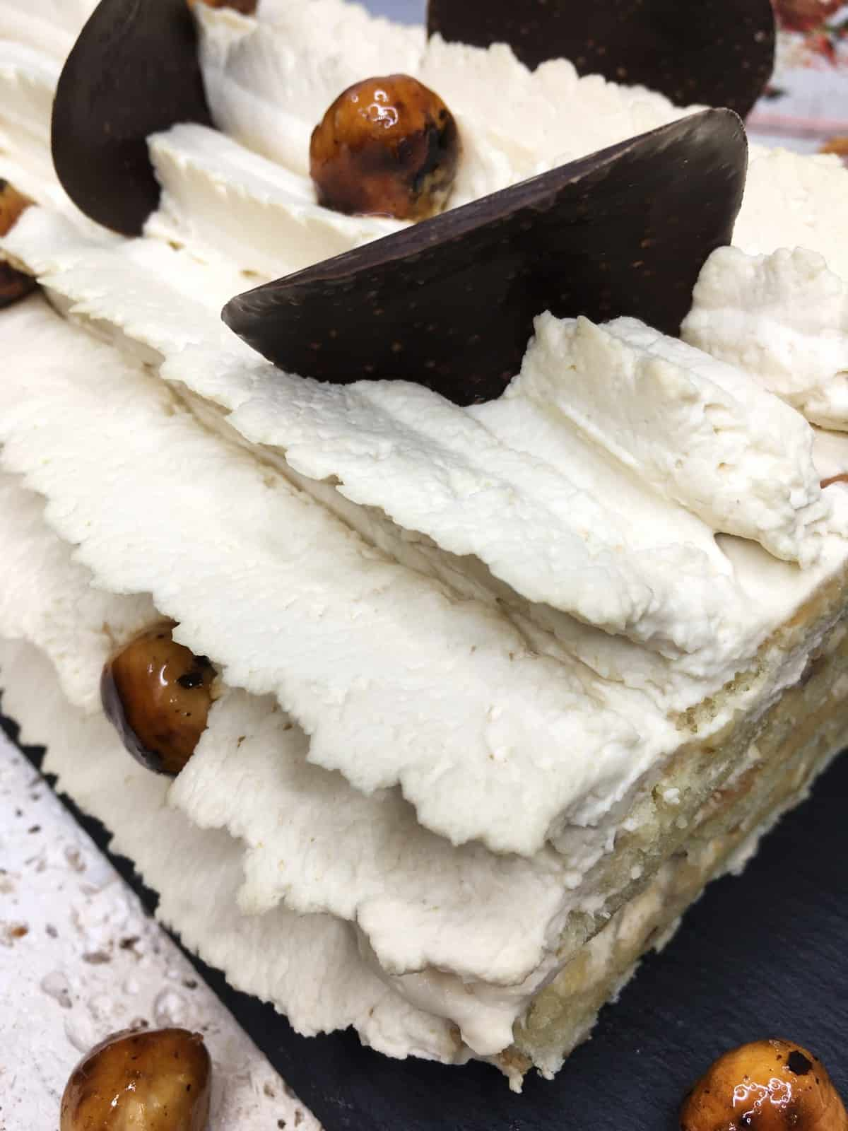 Roll cake covered with coffee cream and decorated with chocolate crisps and caramelized nuts: Close up
