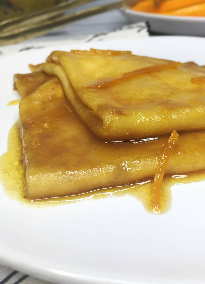 Two crepes Suzette flambe on a white plate with sliced oranges on background