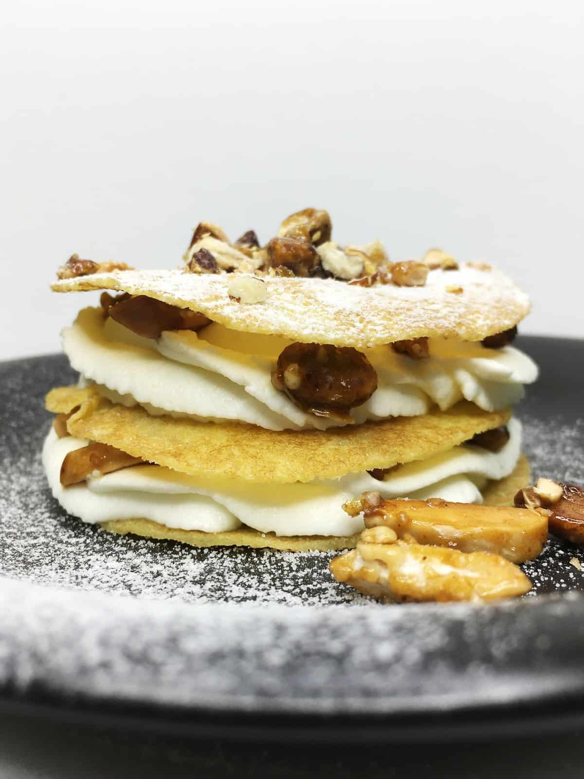 A single French mille crepe (crispy crepes Millefeuille) served on a black serving platter