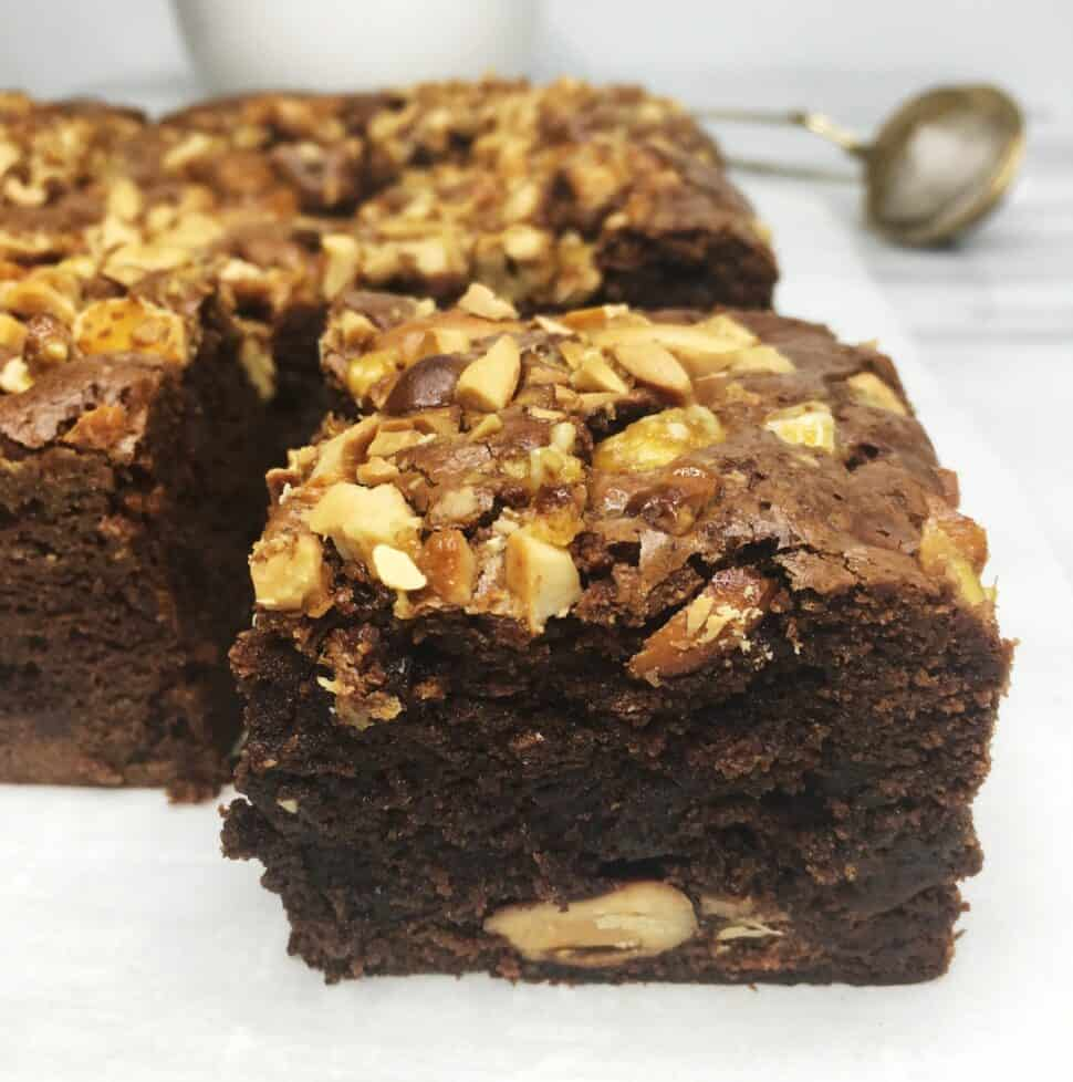 Sliced dark chocolate brownies topped with cashews on parchment