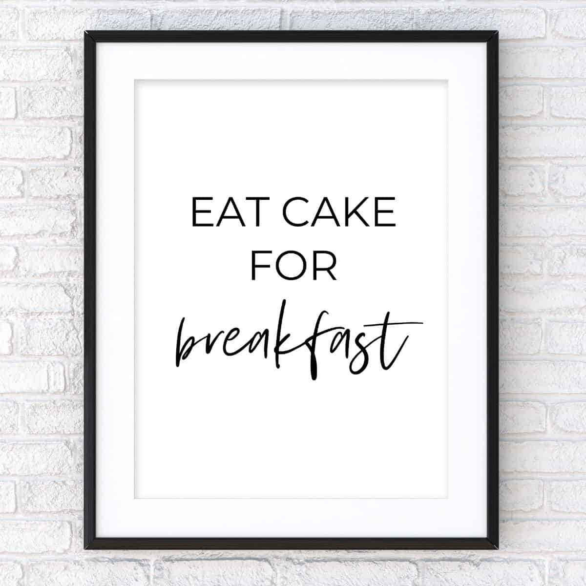 Black frame on the brick wall with the text: Eat cake for breakfast