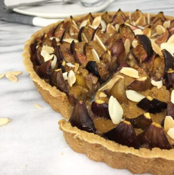 Sliced fig tart on a marble board with plates on background