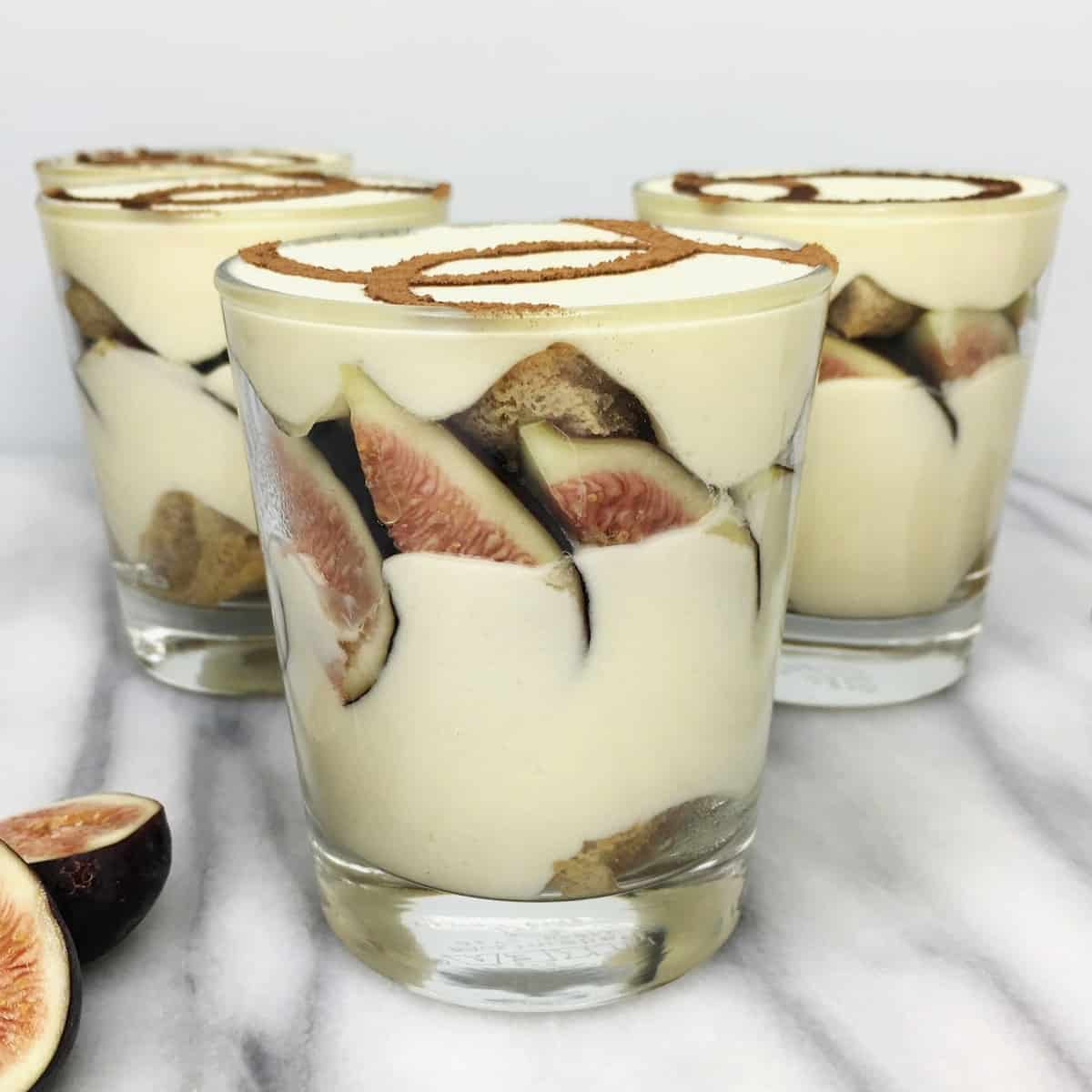 Fig mini tiramisu cups and fig slices on background