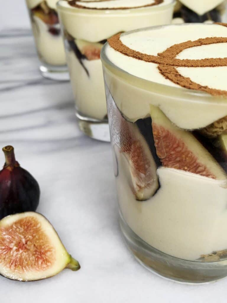 Three tiramisu cups in a row and fig slices on background