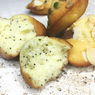 Sliced poppy seed madeleine with the of flavored madeleines on a stone board