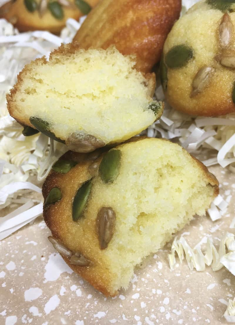 Vanilla-flavored little cakes sprinkled with pepitas and sunflower seeds on a board