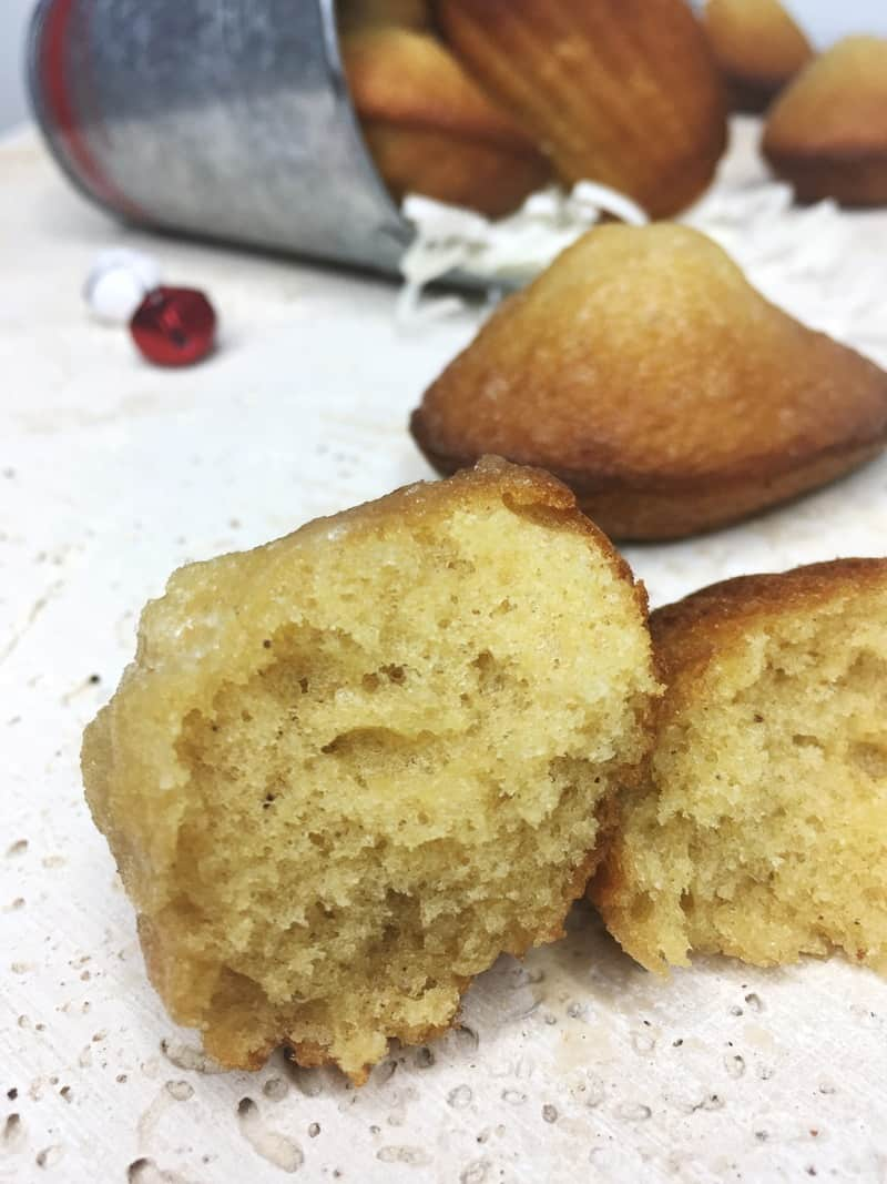Sliced spiced madeleine with the rest of cakes on background