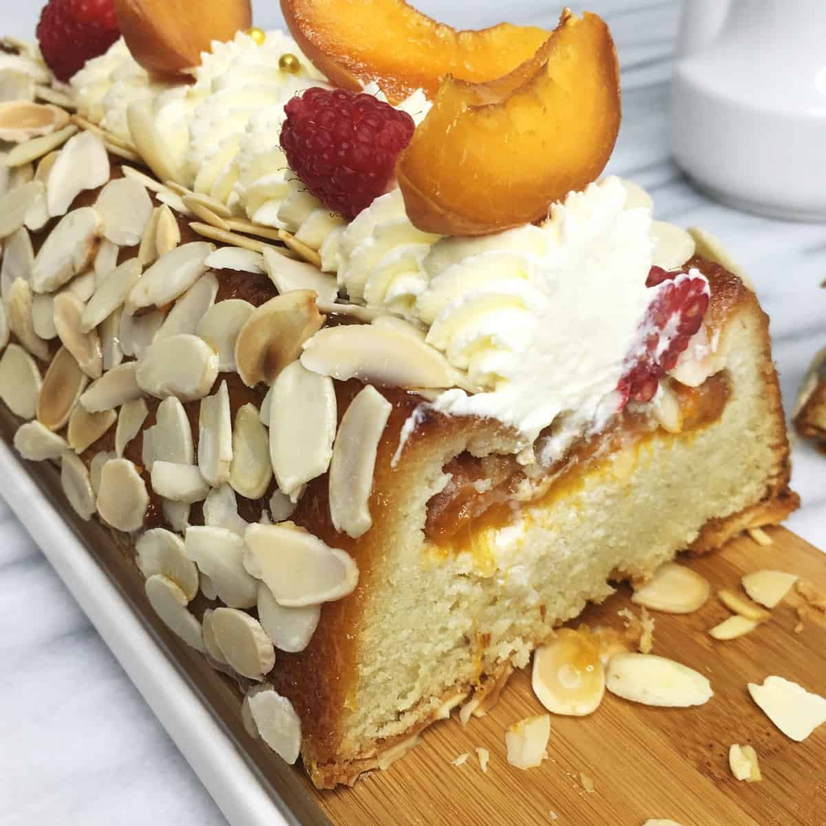 Sliced cake with flaked almonds all over, whipped cream, and apricots on top