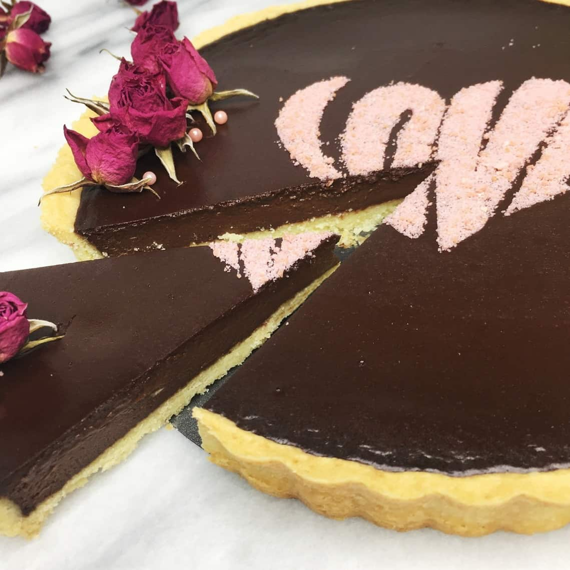 Sliced French chocolate tart decorated with dried rosebuds on a marble table
