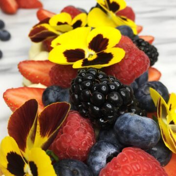 French Mille Feuille cake topped with red fruit and flowers: Close up